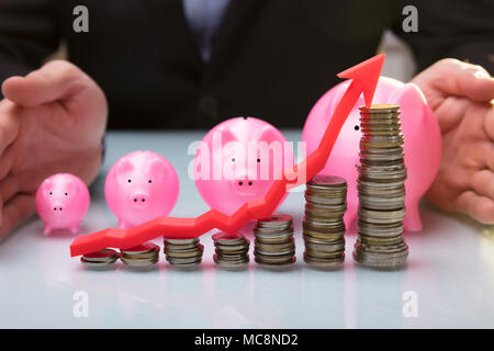 Close-up Of Businessperson Protecting Pink Piggy Bank Behind Stacked Coins And Arrow Showing Upward Direction - Stock Photo