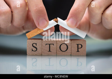 Close-up Of A Person's Breaking Cigarette Over Blocks Showing Stop Text - Stock Photo