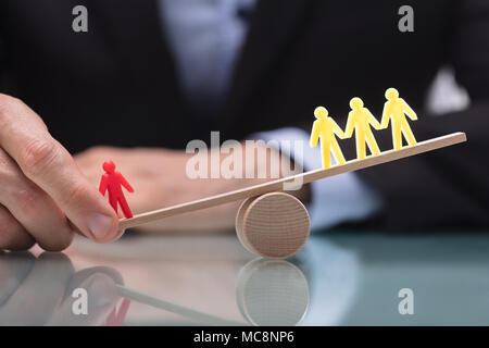 Businessperson's Hand Showing Imbalance Between Red Figure And Three Yellow Figures On Seesaw - Stock Photo