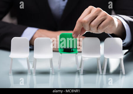 Close-up Of A Businessperson's Hand Choosing Green Chair With Graduation Hat - Stock Photo