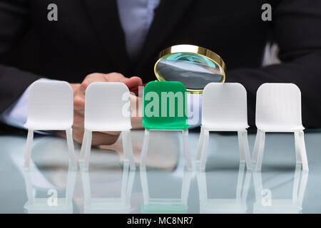 Close-up Of A Businessperson's Hand Looking At Vacant Chairs Through Magnifying Glass - Stock Photo