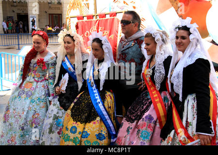 Traditionally dressed up people at the Hogueras de San Juan Festival in Alicante, Spain, posting for a picture - Stock Photo