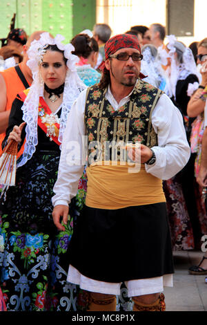 Traditionally dressed up man at the Hogueras de San Juan Festival in Alicante, Spain, eating Tapas - Stock Photo