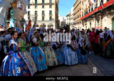 Traditionally dressed up people at the Hogueras de San Juan Festival in Alicante, Spain, posting for a picture in front of a huge figurehead - Stock Photo