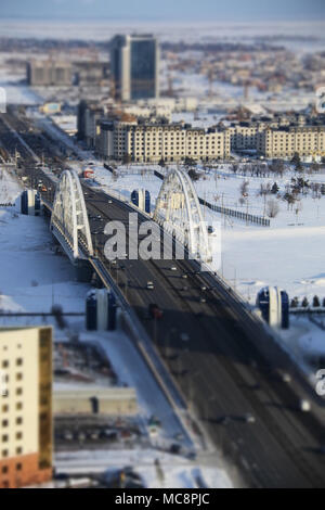 Suspension bridge across the frozen Ishim river in Nur-Sultan, Kazakhstan, at -24 degrees Celsius - Stock Photo
