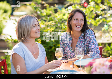 Portrait of two beautiful women in their forties, a brunette and a blonde. They share a terrace meal in the garden with friends - Stock Photo