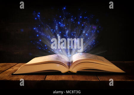 image of open antique book on wooden table with glitter overlay - Stock Photo