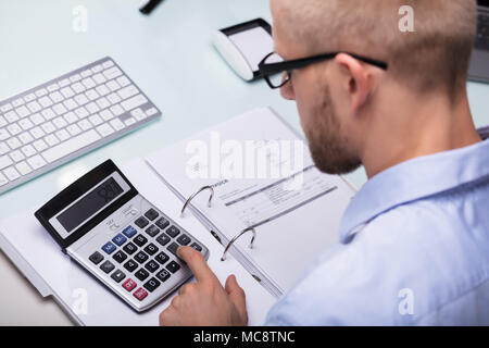 Businessman Using Calculator For Calculating Invoice At Desk - Stock Photo