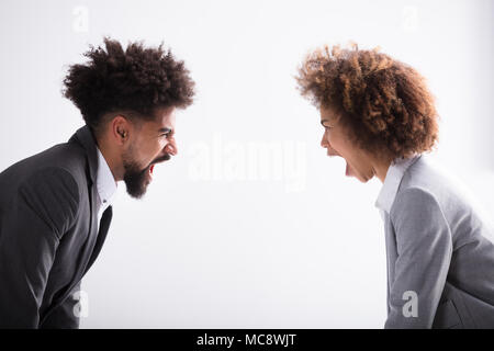 Close-up Of Two Angry Young Business Partner Shouting At Each Other In Office - Stock Photo