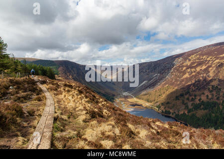 Hikers on walking trial climbing the Spinc ridge over the spectacular Glendalough and Glenealo Valleys in Wicklow Mountains National Park - Stock Photo