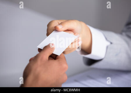 Close-up Of Businessperson's Hand Giving Blank White Card To Partner - Stock Photo