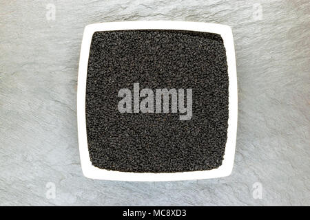 Black cumin (nigella sativa or kalonji) seeds in white plate on white stone background surface with free space - Stock Photo