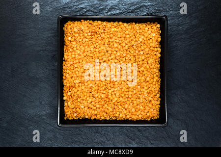 Red lentil grains in black plate on black stone background surface with free space - Stock Photo