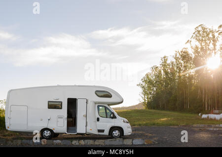 Holiday trip in motorhome. Camper Camping at meadow in Galicia, Spain at sunrise. - Stock Photo