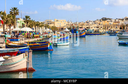 Marsaxlokk, Malta island. Traditional fishing boats luzzus with bright colors anchored at the port of Marsaxlokk - Stock Photo