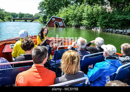 Boat trip on the Ostra Hamnkanalen Malmo, Sweden with tour guide speaking into a microphone and bus crossing the bridge ahead. Space for copy - Stock Photo