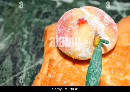 close up of marzipan fruit in shape of peach - Stock Photo