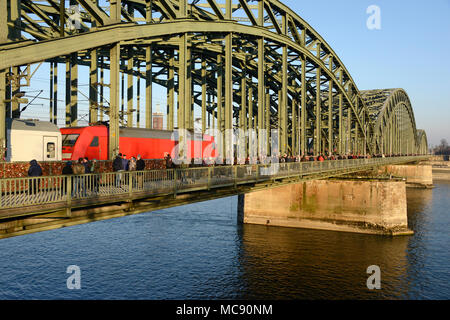A locomotive-hauled train crosses the Hohenzollern bridge in Cologne, Germany heading east as pedestrians walk across on a sunny Sunday - Stock Photo