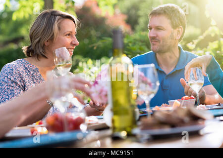 Portrait of a couple in a group of friends gathered around a table in a garden on a summer evening to share a meal and have a good time together. - Stock Photo