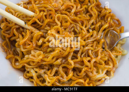Bowl of instant noodles and sauce,chopsticks.  background - Stock Photo