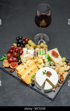 various types of cheese and wine on stone serving board - Stock Photo