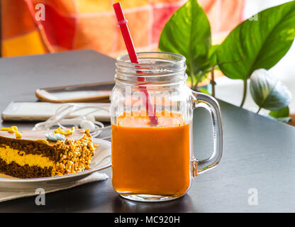 Delicious chocolate cake and smartphone with iced tea glass or orange juice in coffee shop on table blurred background. - Stock Photo
