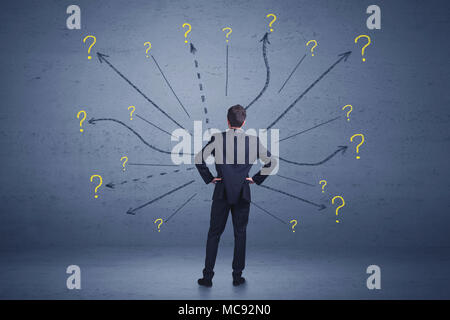 Businessman standing in front lines and question mark signs concept on background - Stock Photo