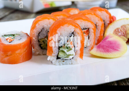 Philadelphia roll sushi with salmon, prawn, avocado, cream cheese  served on wooden background. Sushi menu. Japanese food. Sushi set. - Stock Photo
