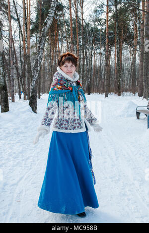 a girl with beautiful hair on her head in a Slavic style in full growth in the winter forest. - Stock Photo
