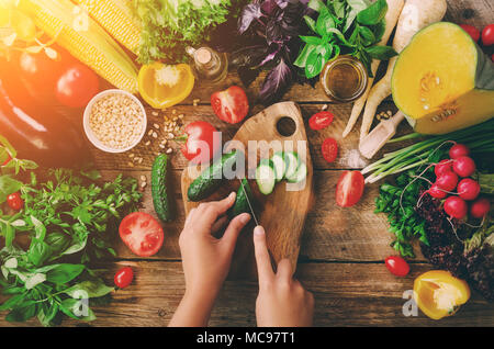 Woman hands cutting vegetables on wooden background. Vegetables cooking ingredients, top view, copy space, flat lay. Sunlight bokeh - Stock Photo