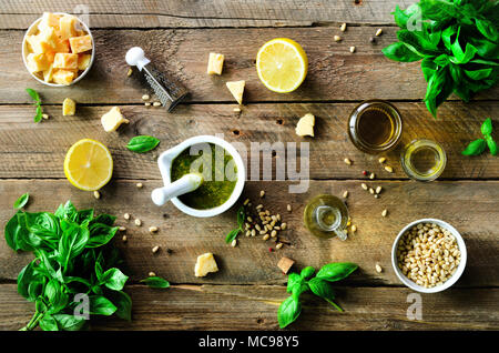 Ingredients for homemade pesto - basil, lemon, parmesan, pine nuts, garlic, olive oil and salt on rustic wooden background. Top view, flat lay, copysp - Stock Photo