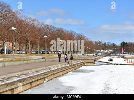 Tourists walk along embankment in early spring - Stock Photo