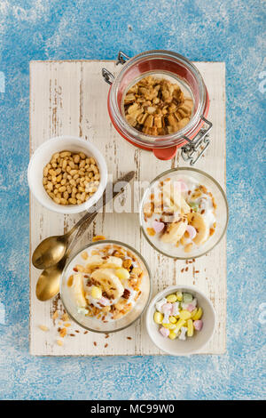 Healthy dessert from yogurt, banana, granola and nuts in glass glasses on a white wooden cutting board on a blue background. Top view - Stock Photo