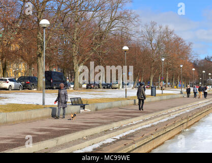 Walk with dog along embankment in early spring - Stock Photo