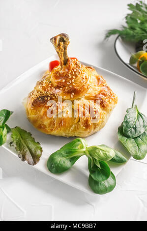Chicken leg leg in the dough with potatoes, tomatoes, onions and spices baked in the oven. - Stock Photo