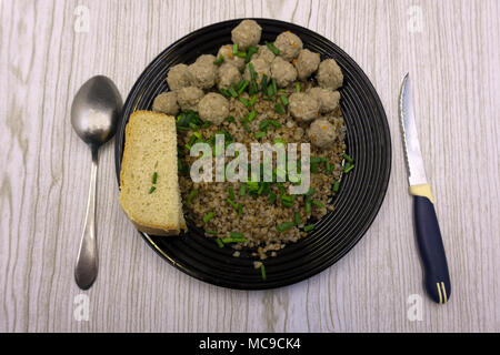 Buckwheat with meatballs and vegetables on a concrete background. Lunch for the whole family - Stock Photo