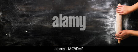 Girl hands keep rolling pin with flour on dark black table, baking background, top view, copy space for your text, meru, recipe. Banner - Stock Photo