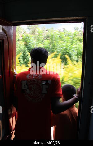 Taking a scenic train ride from Ella to Kandy, passing some stunning landscapes. Two men standing in the open door of the carriage. - Stock Photo