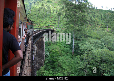 Taking a scenic train ride from Ella to Kandy, passing a thrilling truss bridge - Stock Photo