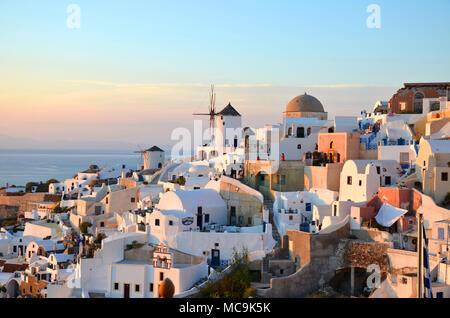 Oia, Santorini / Greece: A view of the coastal village of Oia at sunset on the island of Santorini, Greece - Stock Photo