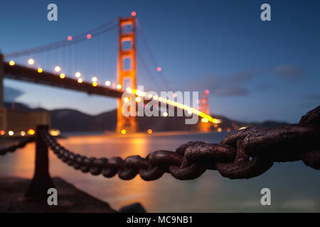 A suspenseful focus on the rust of a chain in front of the Golden Gate Bridge. - Stock Photo