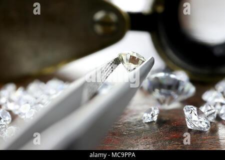 brilliant cut diamond held by tweezers - Stock Photo