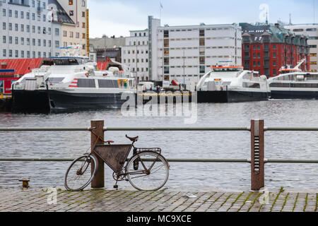 Old bicycle parked on the embankment in Bergen port, Norway - Stock Photo