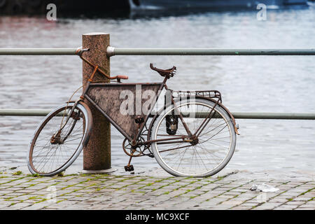 Old rusted bicycle is on the embankment in Bergen harbor, Norway - Stock Photo