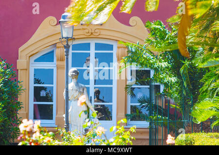 Gardens in European style adorned with statues, lamps and windows that reflect the silhouette of a beautiful statue. - Stock Photo