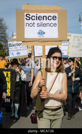 14 April 2018, Germany, Munich: A woman protests and carries a sign reading 'Science not silence' during the 'March for Science'. Around the world there are rallies on Saturday, where people stand up for the liberty of research and teaching. Photo: Matthias Balk/dpa - Stock Photo