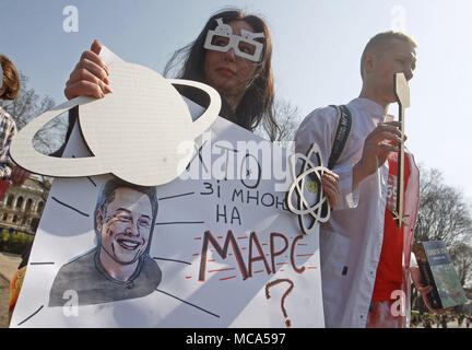Kiev, Ukraine. 14th Apr, 2018. A woman holds a poster with an image of CEO of SpaceX and Tesla Motors Inc. Elon Musk and reading like ''Who is with me on Mars?'', during costumed march-performance ''March For Science'' in center of Kiev, Ukraine, on 14 April 2018. Popularizers of science, physicists and adherents of science took part in the global action ''March For Science'' for the liberty of research and teaching, during the rallies, that took place around the world on Saturday Credit: Serg Glovny/ZUMA Wire/Alamy Live News - Stock Photo