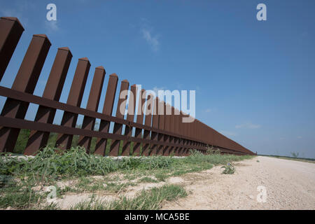 An unfinished section of the security fence between the United States and Mexico sits atop a levee of the Rio Grande River on the Texas side of the international border in Hidalgo County. - Stock Photo