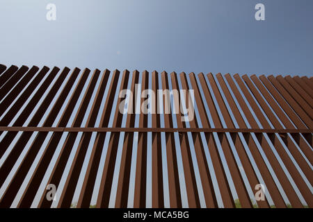 A section of the security fence between the United States and Mexico sits atop a levee of the Rio Grande River on the Texas side of the international border in Hidalgo County. - Stock Photo