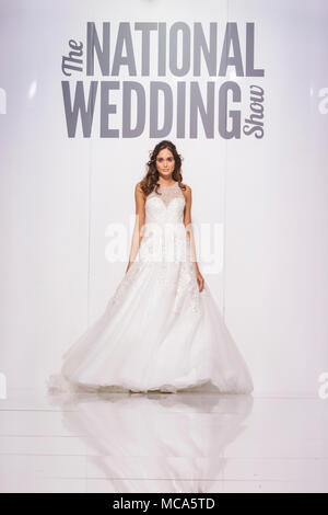 ExCel London, London, 14th April 2018. Dresses from 'Bromley Brides' on the catwalk. The National Wedding Show takes place at ExCel London Exhibition Centre this weekend, showcasing the latest bridal trends, accessories, dresses and everything around planning the perfect wedding. Credit: Imageplotter News and Sports/Alamy Live News - Stock Photo
